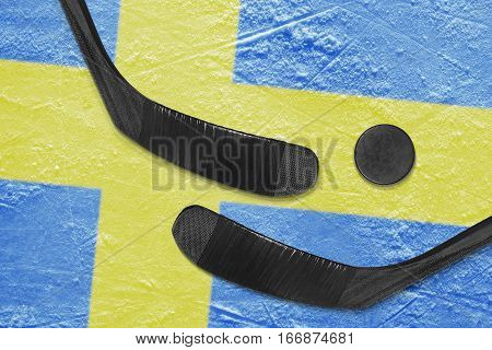 Hockey puck hockey sticks and a picture of the Swedish flag on the ice. Concept
