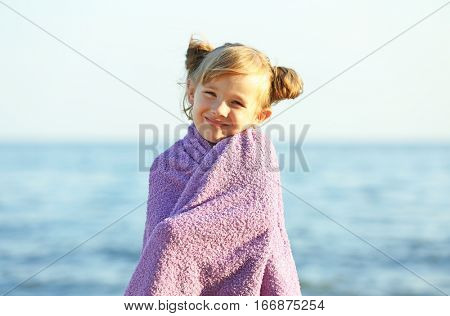 Cute girl wrapped in towel on beach