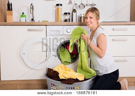 Young Woman Loading Clothes Into Washing Machine In Kitchen