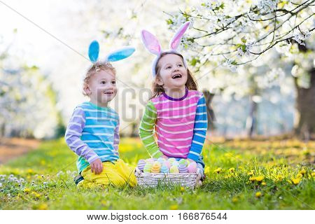 Easter Egg Hunt. Kids With Bunny Ears In Spring Garden.