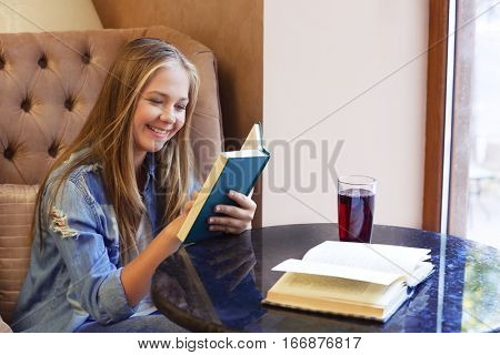 Pretty teenager girl reading books while sitting in cafe