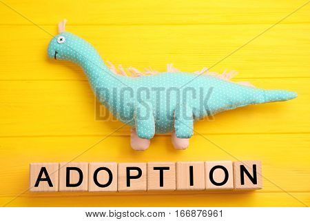 Cubes with word ADOPTION and dinosaur toy on color wooden background
