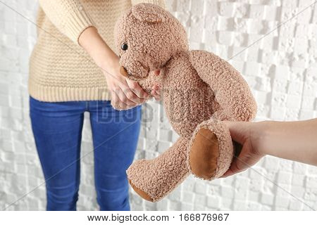 Child custody concept. Closeup of girl holding teddy bear on white textured background