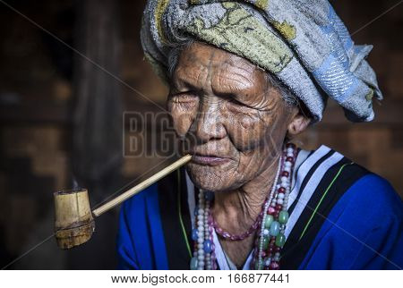 Chin region Myanmar November 11 2014: muun tribe chin lady in her kitchen smoking her pipe