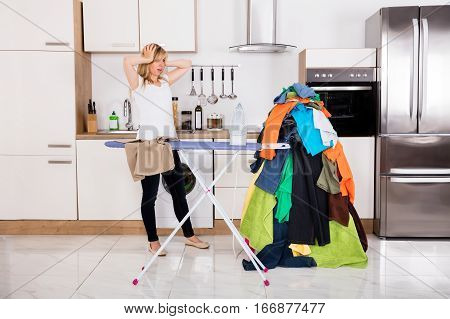 Young Frustrated Woman Looking At Pile Of Clothes For Ironing Near Ironing Board At Home