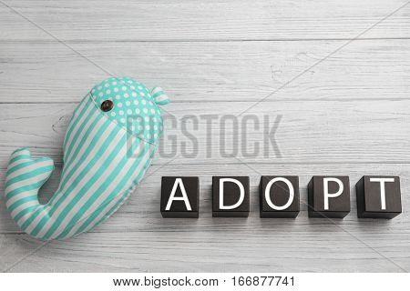 Cubes with word ADOPT and whale toy on light wooden background