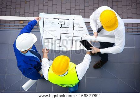 Engineer and workers discussing project of new building