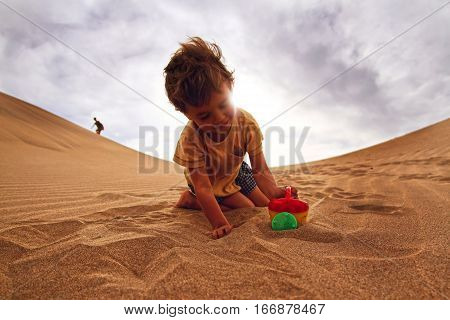 Babyboy playing in a desert playind with sand