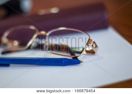 Ballpoint Pen On A Sheet And Reading Glasses With Box