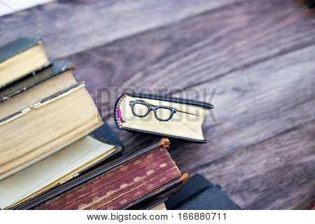 Vintage books and bookmark glasses on a brown wooden background