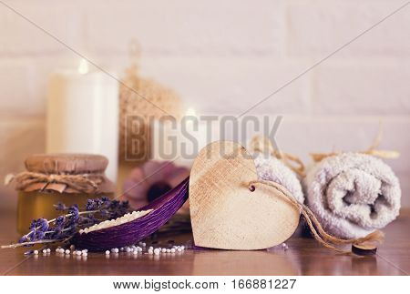 Spa And Wellness Setting With White Towels , Sponge, Candle, Lavender And Wooden Heart On Bricks Wal
