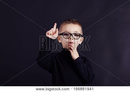 Studio Portrait Of Watchful Child In Pullover And Glasses