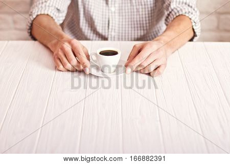 Coffee Break. Man Sitting On The White Table With Cup Of Espresso In The Checked Shirt. White Bricks