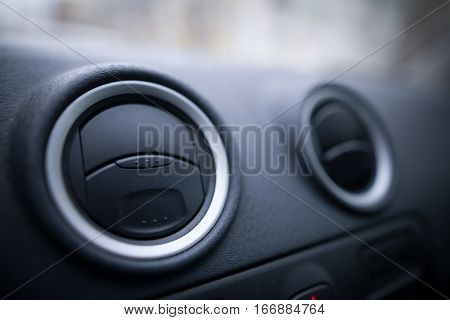 Close up shot of a the air vents inside a car.