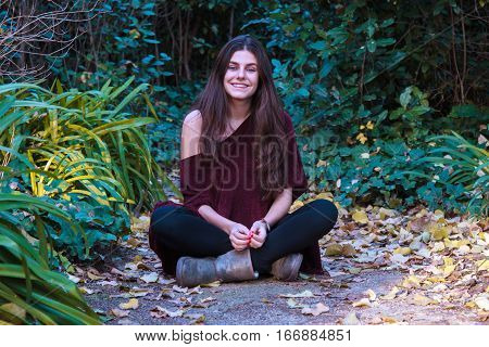 Young white woman with blue eyes and brown hair sitting on the floor of a path in a forest on a sunny autumn day. She is happy and smiling while enjoying a day outdoors.