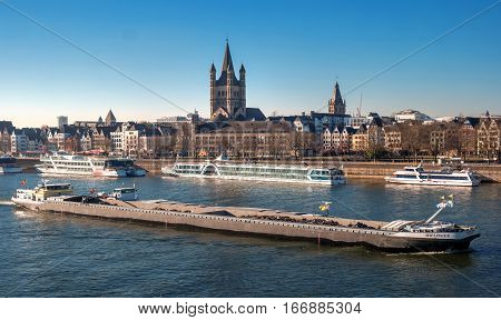 Cologne, Germany - January 19, 2017: Historic center of Cologne at dusk with Gross St. Martin and town hall. On the Rhine River are walking ships.