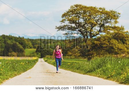 Kid girl running down the road in countryside on a very hot day, image taken in Canton of Vaud, Switzerland