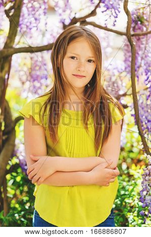 Outdoor stylish portrait of a cute little girl of 8-9 years old, standing next to beautiful purple wisteria flowers, wearing green blouse