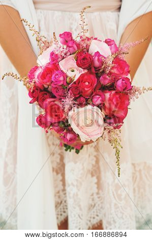 Tender bouquet of pink roses and light lavender in bride's hands