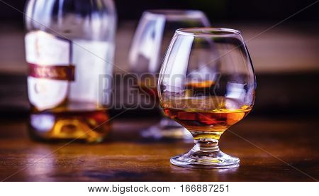 Glass whiskey cognac brandy or rum.One half full glasses of cognac on a wooden surface.