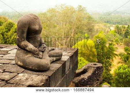 Portrait of Headless Buddha from the side with view of surrounding Landscape