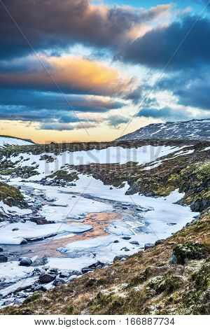 A frozen river in the highlands of Iceland framed by pastel skies and rugged terrain offers scenic landscape epitomizing the frozen wilderness.