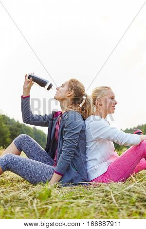 Thirsty young women sitting on the grass after making sport