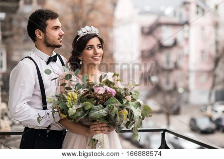 The bride and groom embrace on the balcony. Couple hugging on the balcony and enjoy life