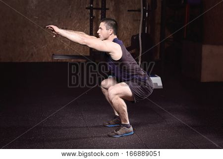 Young handsome man doing squats in gym