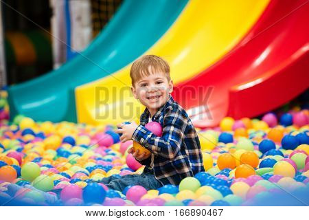 Cheerful little boy sitting and playing at indoor playground with colorful balls