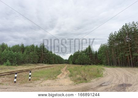 The old railway line and the dirt road in the forest. Russia.