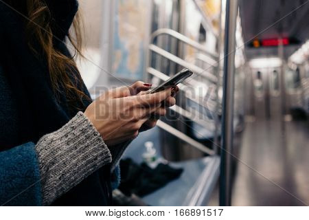 Close up of a women hands holding mobile phone in subway train