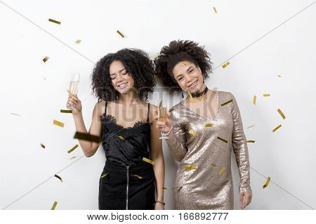 Two women holding glasses of champagne, enjoying a party
