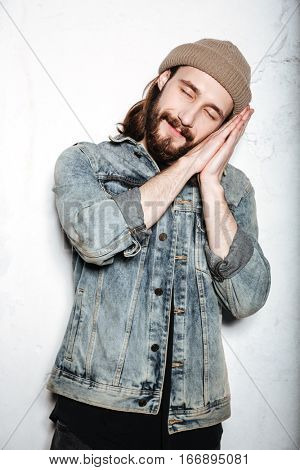 Photo of young cheerful bearded hipster man wearing hat dressed in jeans jacket sleeping on hands over wall background.