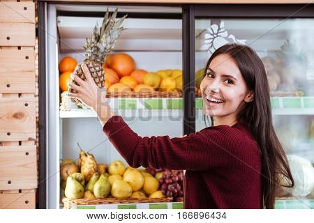 Cheerful young woman choosing and buying pineapple in grocery shop
