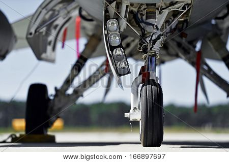 Military aircraft detail with landing gear and engine cover on a runway