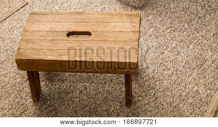 Small four legged wooden step stool on carpet.