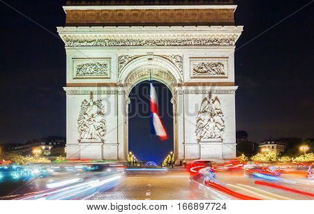 The Triumphal Arch decorated with National flag Paris France.