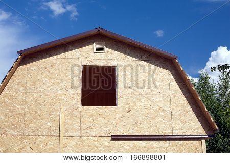 Suburban house construction with OSB on sunny summer day