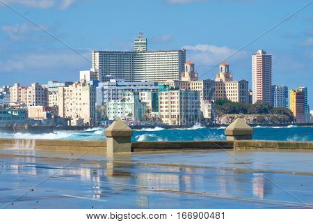 The Havana skyline with waves crashing on the Malecon seawall