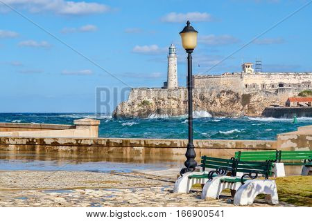 The fortress and lighthouse of El Morro in Havana seen from a park across the bay
