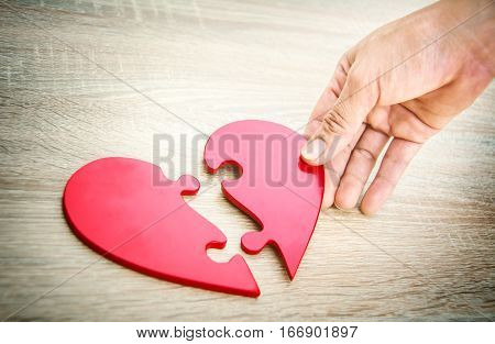 female hand matching red jigsaw heart halves on grey wooden background