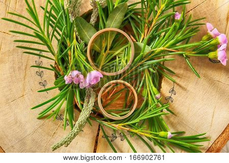 Composition of beautiful boutonniere and wedding rings, closeup