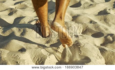 Male feet walking on sand. Tanned man crossing desert barefoot. Human footsteps on beach. Survival on uninhabited island concept. Back view.