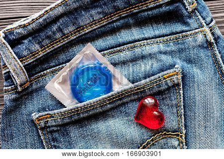 concept male contraception condom in jeans pocket.