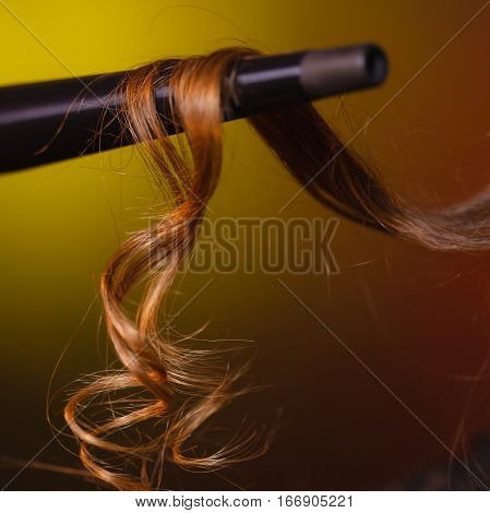 Haircare hairstyiling at home concept. Closeup of brown hair on iron curler. Studio shot on dark colorful background