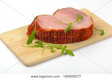 stack of sliced smoked pork meat with arugula leaves on wooden cutting board