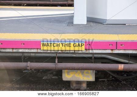 Platform at a long island railroad station has a warning sign which states watch the gap.