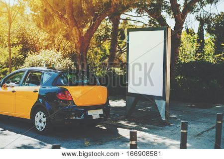 Blank billboard with copy space for your text message near yellow taxi public information board in city advertising white mock up empty banner at beautiful sunny day in front of park or garden