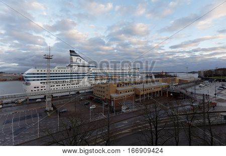HELSINKI, FINLAND - NOVEMBER 26, 2016: Traffic at Olimpia terminal with cruiseferry Symphony of Tallink Silja Line moored. Built in 1991, the ship has passenger capacity of 2800